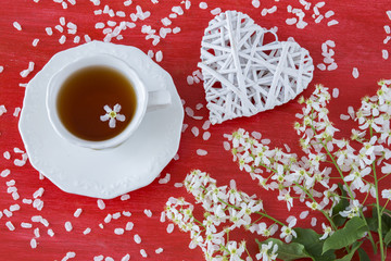 on a red background a branch of cherry, a cup of tea and a decor heart of white twigs