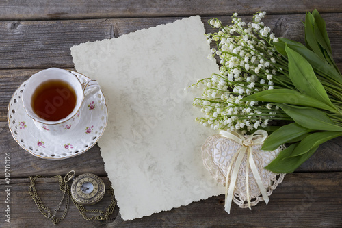 6d657dc24 on a wooden background lilies of the valley, a cup of tea, an old ...