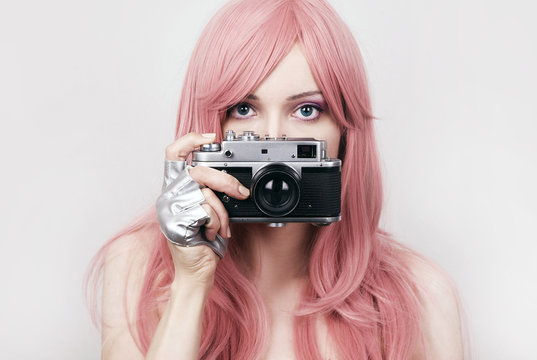 Young woman with pink hair holding retro camera
