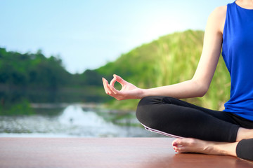 Young woman wear blue shirt exercising and sitting in yoga lotus position with nature background