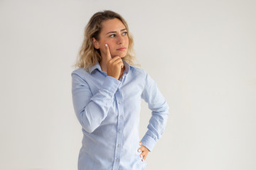 Portrait of young thoughtful Caucasian businesswoman. Woman wearing blue shirt looking away with pensive expression. Contemplation concept