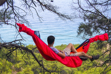 young man tourist in a hammock in the mountains looking at the sea