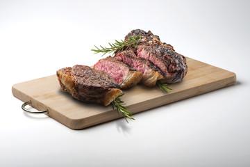 Fiorentina T-bone steak cut on rectangular wooden chopping board