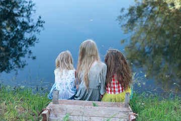 children on the riverbank / summer vacation merry girlfriends on vacation, sisters together on the river, friendship happiness family