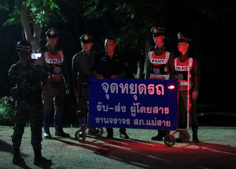 Police officers pose for a photo near Tham Luang cave complex in the northern province of Chiang Rai