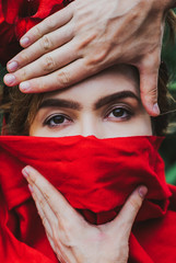 Beautiful young woman covered in red headscarf by man's hands