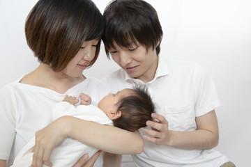 新生児を抱き見つめる若い夫婦、幸せな家族イメージ