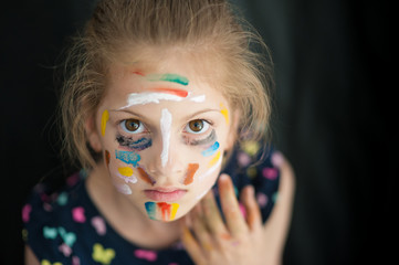 afraid pretty little girl with face painted with various colors copyspace