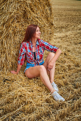 Portrait of young redhead woman in jeans shorts