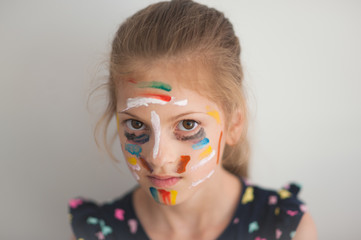 portrait of cute caucasian little girl with face painted with various colors