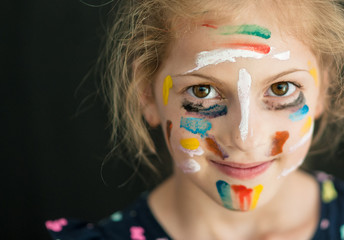 pretty caucasian little girl with face painted with various colors copyspace