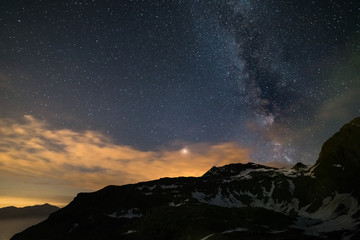Astro night sky, Milky way galaxy stars over the Alps, stormy sky, Mars planet beyond the clouds, snowcapped mountain range