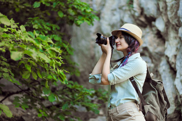 A tourist girl in a hat takes pictures of nature in the mountains.