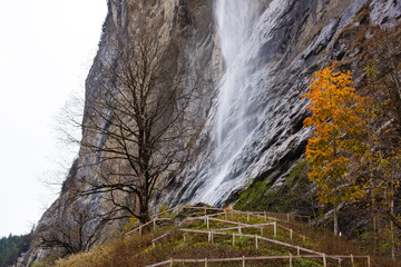 Wall Mural - Beautiful autumn time at village of Lauterbrunnen in Swiss alps, gateway to famous Jungfrau. Set in a valley featuring rocky cliffs and the roaring