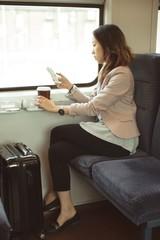 Female executive using mobile while having coffee