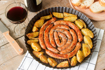 Aromatic meat sausages with potatoes, salad and wine on a wooden background. Selective focus.