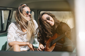 Two women with guitar in the old van