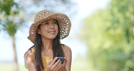Woman wearing hat straw and taking photo by cellphone at outdoor