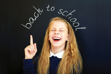 Happy laughing school child near school blackboard