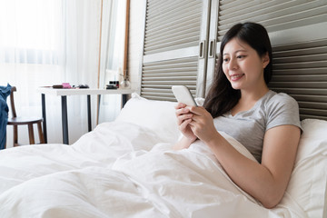 woman lying in the bed and using her cellphone