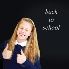 Happy little  school girl near school blackboard