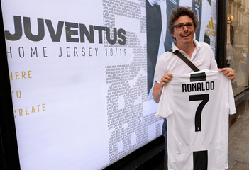 A Juventus supporter holds, after buying, the first original Juventus' jersey printed with the name and number of Cristiano Ronaldo after his transfer to Juventus in Turin