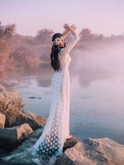 A river nymph in a white lace dress stands on a rock by the lake. The princess has a beautiful wreath with seashells. The background is a fabulous dawn and an early mist over the river in rose tones.