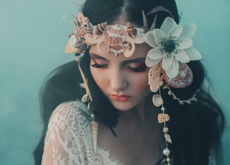 Close-up portrait - makeup of a river nymph, in gentle green, yellow, peach hues. The brunette girl with an unusual wreath with seashells. Puppet's baby face. Background thick fog.