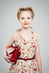 Beautiful blonde woman with retro hairstyle, fashionable makeup, handbag and dress pinup