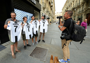 Juventus supporters pose as they hold, after buying, the original Juventus' jersey printed with the name and number of Cristiano Ronaldo after his transfer to Juventus in Turin
