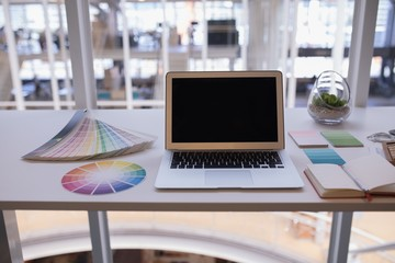 Laptop and color swatch at desk