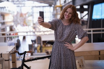 Happy female executive taking selfie with mobile phone