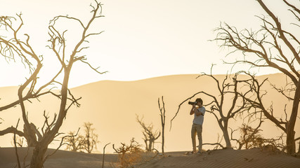 Young male traveler and photographer in photographing pose surrounded by dead tree during sunset in desert, travel photography concept