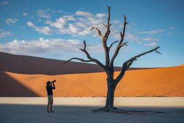 Young man photographer and traveler standing between dead trees in deadvlei (Sossusvlei) during sunrise, famous natural landmark in Namib desert of Namibia, Africa