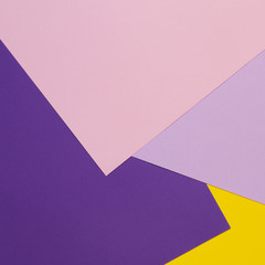 Color papers geometry flat composition background with violet, purple, pink, yellow tones.