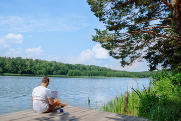 man working on laptop while sitting on wooden dock. legs in river water