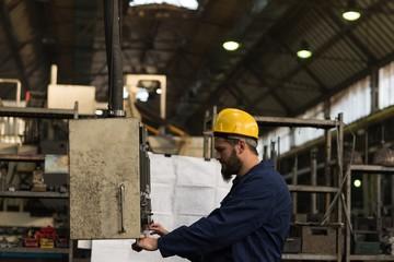 Technician checking machine in factory