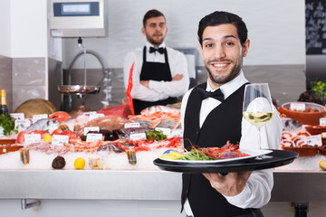 Waiter with serving tray in fish restaurant