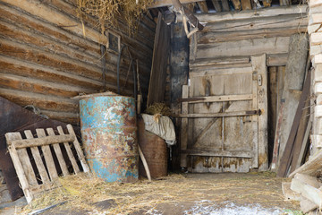 old abandoned barn with metal barrels and old things