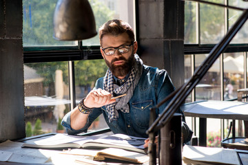 Lviv city, Ukraine, June 06, 2018  young architecture man with a beard in a denim shirt and scarf working at a table with a drawing