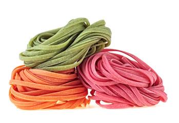 Italian pasta tagliatelle on white background. Colorful pasta nests.