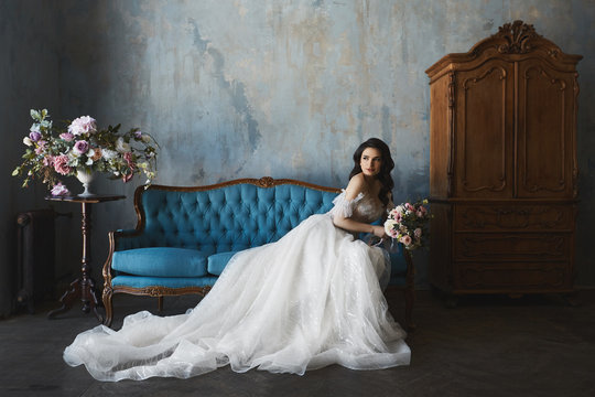 Sexy and beautiful brunette model girl in stylish and fashionable lace wedding dress with naked shoulders sits on the antique sofa and posing in luxury vintage interior