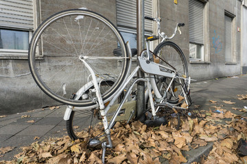 A broken bicycle tied to a lamppost on the sidewalk among the yellow maple leaves. Autumn in Europe