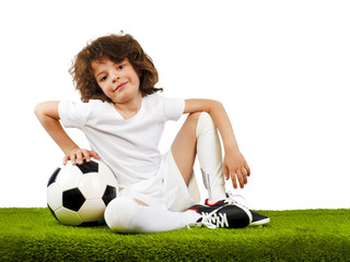 Young European boy, fan or player in white uniform with soccer ball sitting on green grass, cheer favorite football team. Sport play football, lifestyle concept. Isolated on white