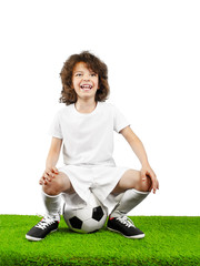 Cool little boy sitting on a soccer ball on white background
