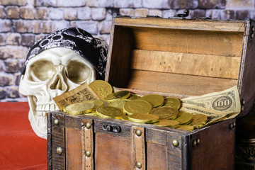 human skull with black skull cap next to wood chest full of gold coins and old paper money on red with brick wall background