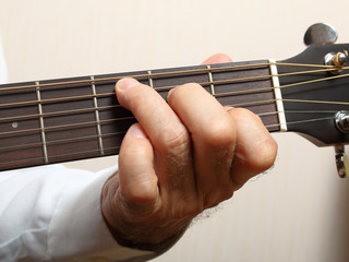 The musician in a white shirt playing acoustic guitar. Left hand on guitar neck
