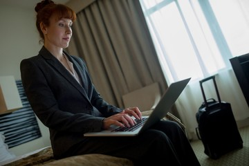 Businesswoman using laptop on bed