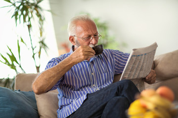 Senior man at home reading newspaper and holding cup of coffee
