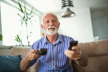 Senior man enjoys watching tv at home.Senior man watching tv and drink coffee